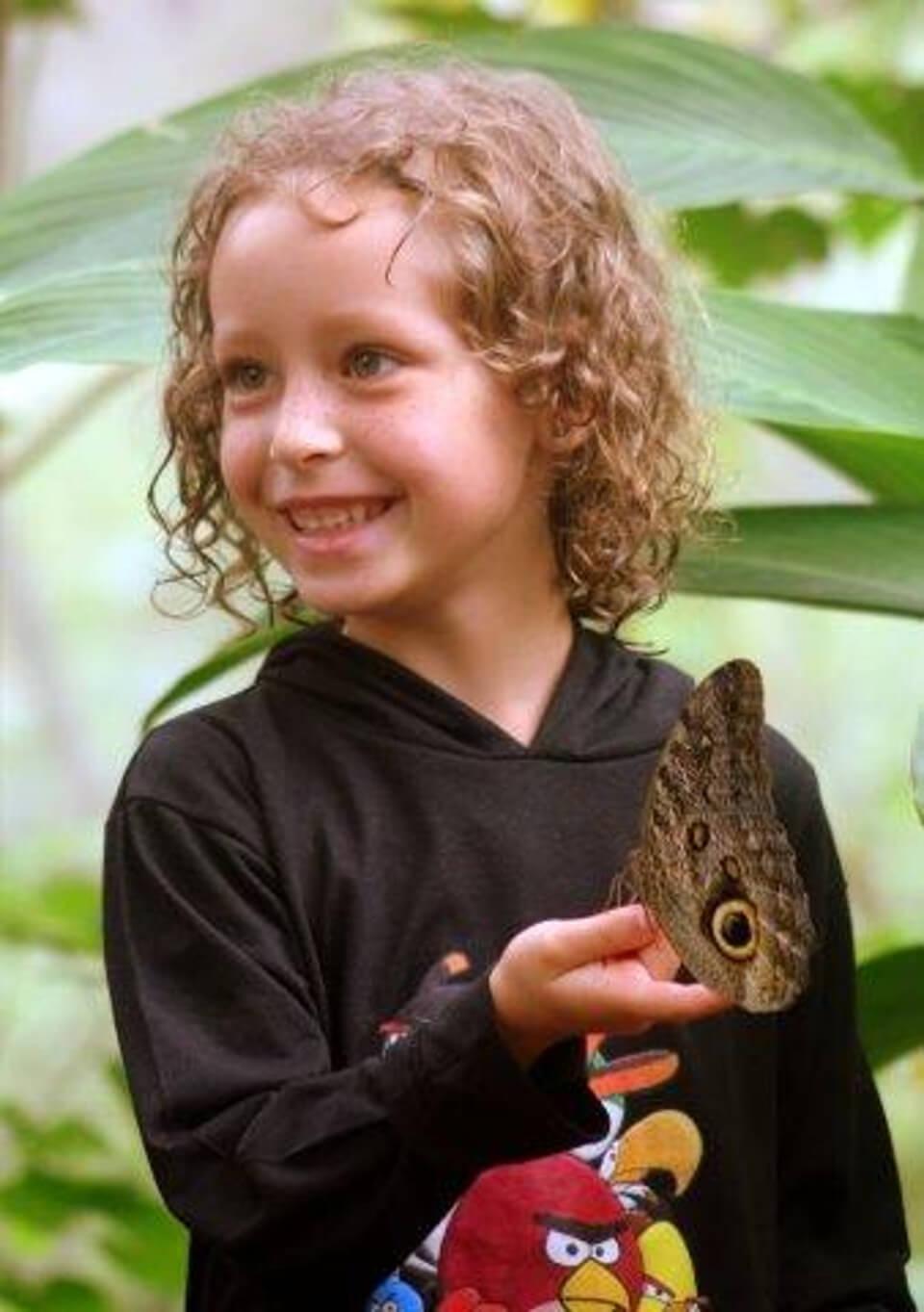 Niño en el Centro de Vida con una mariposa búho